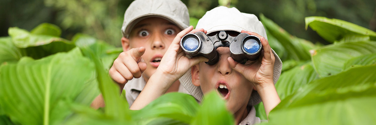 Kinder mit einem Kinderfernglas auf Spionage