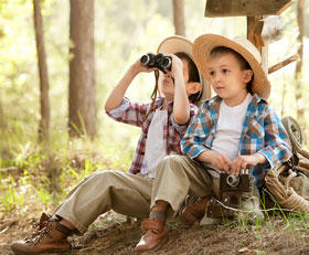 Kinder mit Fernglas im Wald